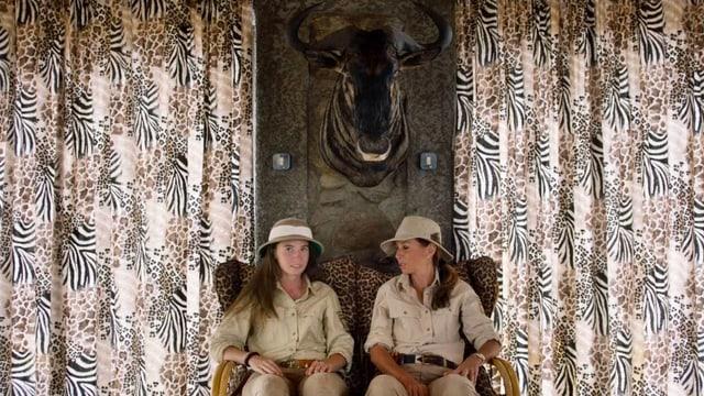 Zwei Frauen sitzen nebeneinander. Über ihnen hängt eine Jagttrophäe.