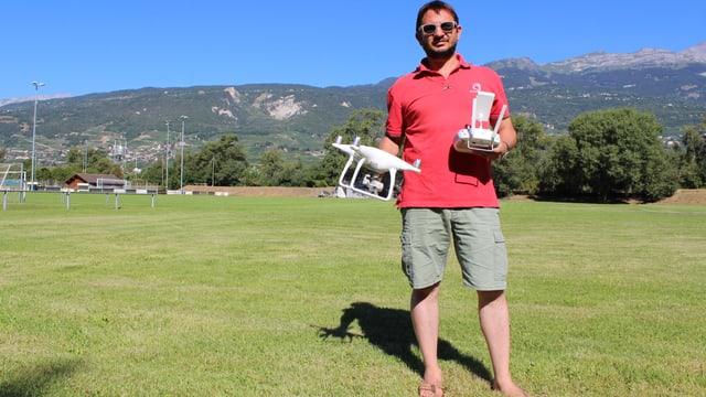 Frédéric Hemmeler auf dem Sportplatz, eine weisse Drohne in der Hand.