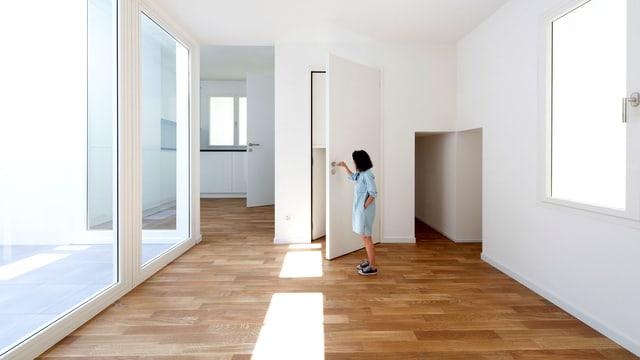 Eine Besucherin öffnet im Schweizer Pavillon eine überdimensionierte Tür.