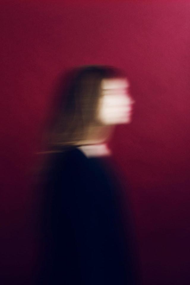 Unscharfes Bild einer Frau vor rotem Hintergrund