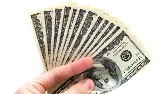 Eine Hand mit vielen 100-Dollar-Scheinen