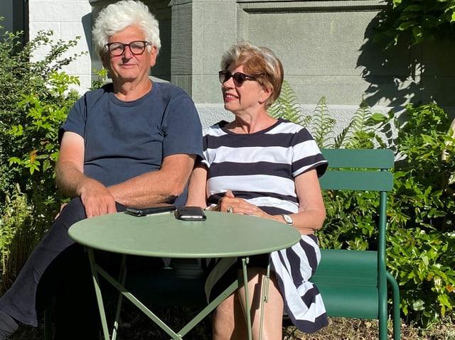 Ein Mann und eine Frau auf einer Bank vor einem Tisch