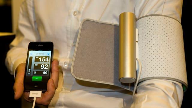 Das Smartphone erfasst die gemessenen Blutdruckwerte und überspielt sie auf Wunsch zur Webseite eines Arztes.