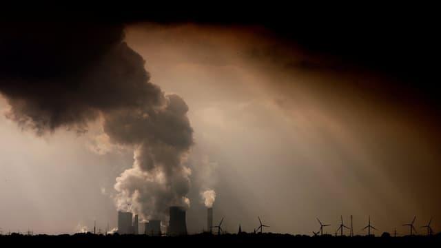 Rauch steigt Kohlekraftwerken im deutschen Niederaussen, davor Windräder.