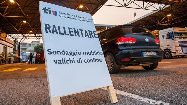 Plakat an Strassenrand stehend, Auto vorbeifahrend, im Hintergrund ist ein Schweizer Zöllner erkennbar.