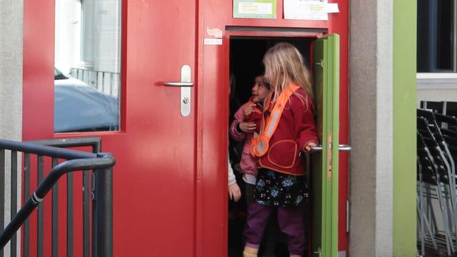 Zwei Kinder verlassen das Kindertheater aus einer kleinen Tür.