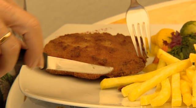 Ein Cordon Bleu auf einem Teller mit Pommes Frites.