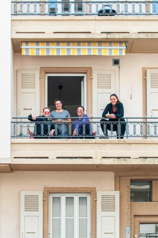 Vier junge Frauen stehen und sitzen auf einem Balkon.
