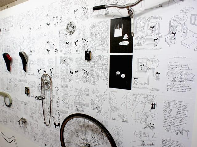 Comicbilder und Veloteile an einer weissen Wand.