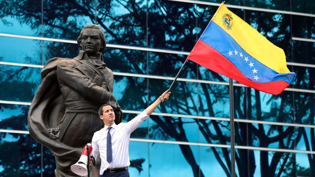 Juan Guaidó schwenkt eine venezolanische Fahne