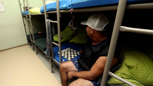 Asylbewerber sitzt auf einem Bett in einer Zivilschutzanlage.