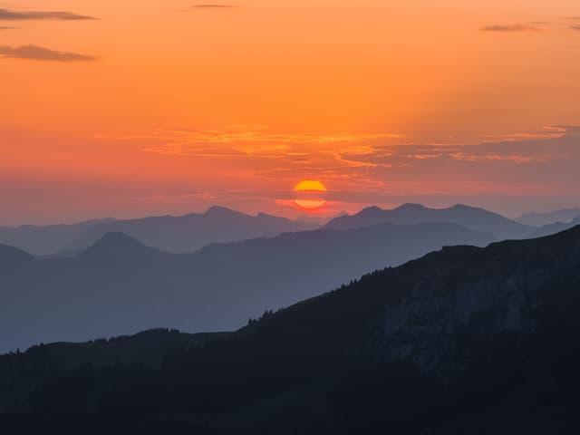 Roter Sonnenaufgang hinter bläulichen Bergen.
