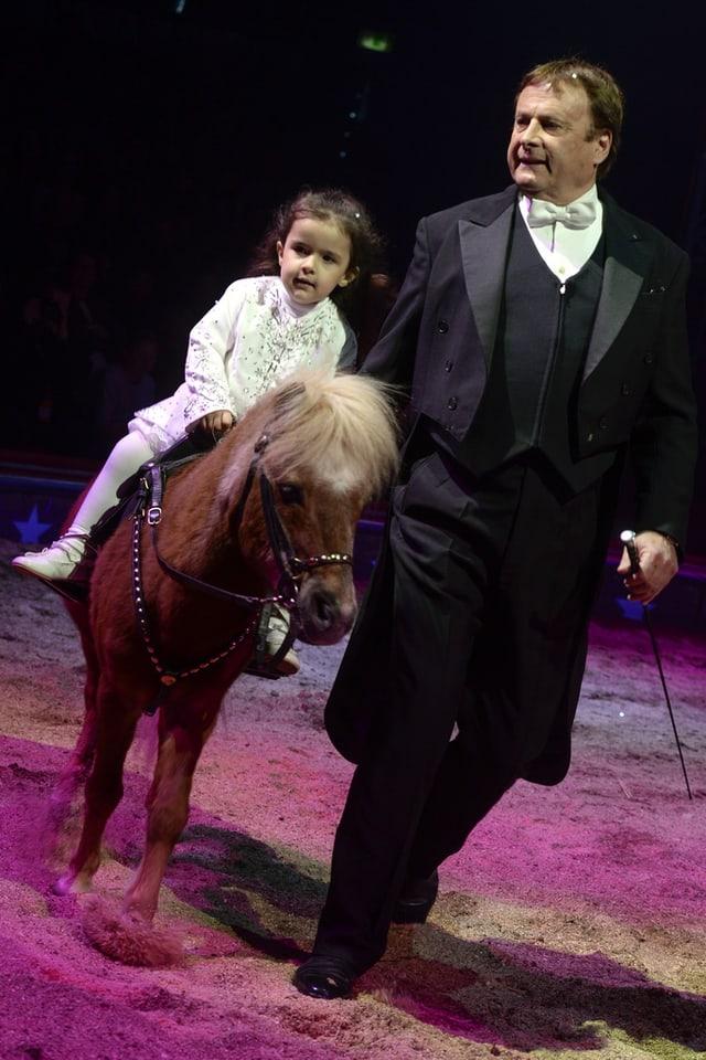 Mann mit Frack und Mädchen auf Pony
