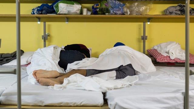 Zwei Menschen schlafen in einer Unterkunft.
