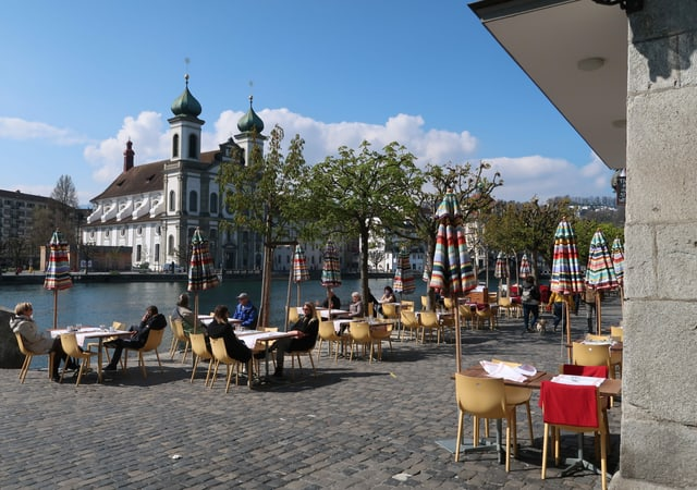 Personen an Tischen am Luzerner Reussufer.