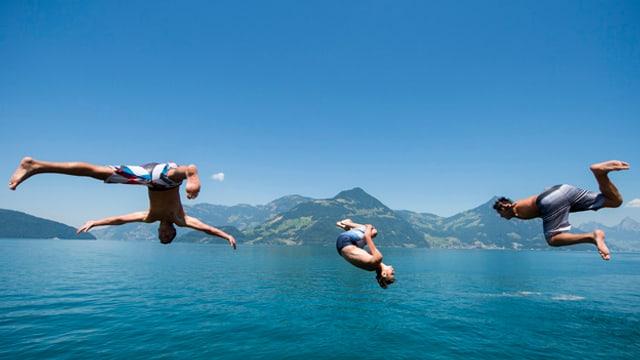 Drei junge Männer springen kopfüber in den See.