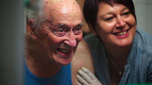 Ein älterer, pflegebedürftiger Mann, daneben seine Pflegerin, beide lachen.