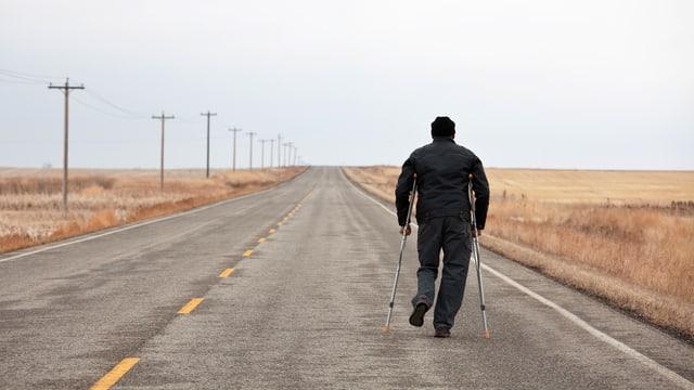 Mann mit Krücken geht Strasse entlang.