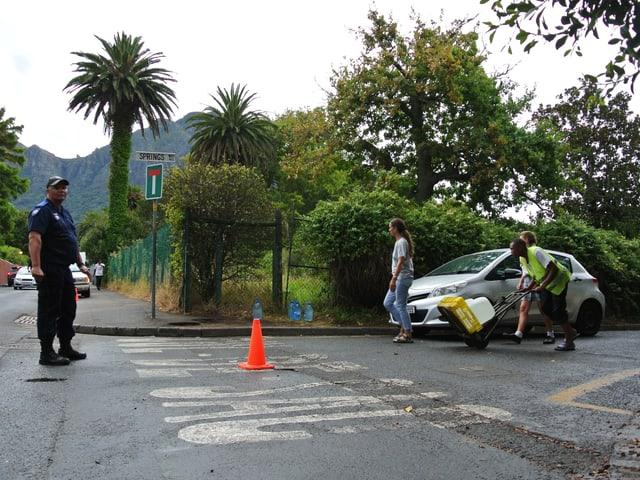 Ein Polizist steht auf der Strasse, während mehrere Personen ein Wägelchen mit Wasserkanistern vorbeischieben.