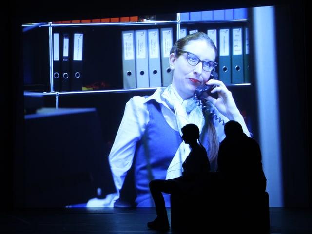 Zwei Personen sitzen im Dunkeln vor einer Leinwand, die mit einem Film bespielt wird.