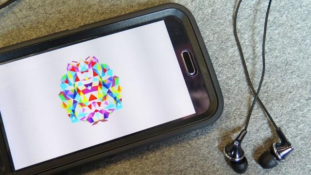 Der Screen eines Smartphones mit einem farbigen Bild. Daneben liegen Kopfhörer.