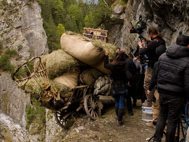 Ein voller Holzwagen ist vom Weg abgekommen und hängt über dem Abgrund.