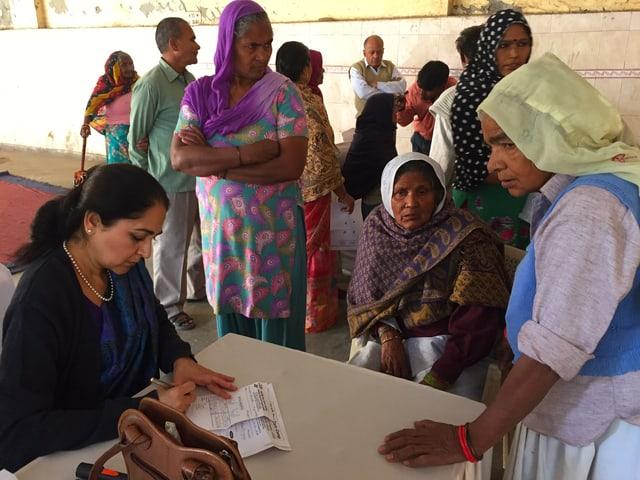 Eine Augenärztin füllt ein Formular aus, um ihren Tisch stehen Frauen aus dem Dorf.