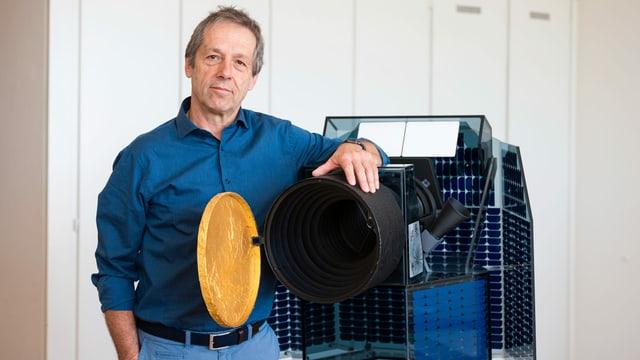 Ein Mann in blauem Hemd steht neben einem Modell eines Satelliten.