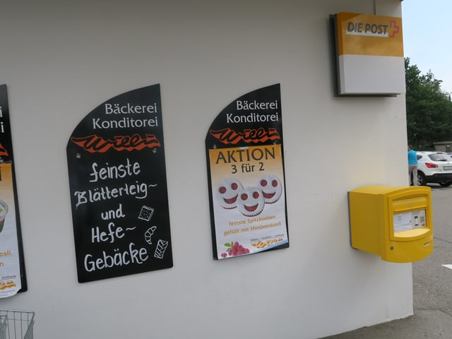 Aktionstafeln einer Bäckerei und ein gelber Briefkasten der Post.
