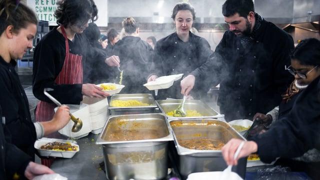 Viele junge Leute schöpfen Essen aus dampfenden Behältern.