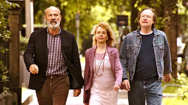 Zwei Männer und eine Frau gehen eine Strasse entlang.
