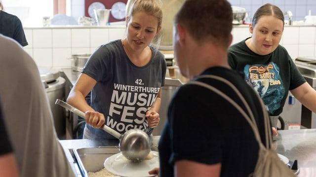 """eine junge Frau schöpft mit grosser Kelle Essen, sie trägt ein dunkles T-Shirt mit der Aufschrift """"Winterthurer Musikfestwochen"""""""