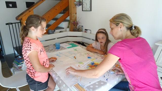 Zwei Mädchen und eine Frau, die an einem Tisch sitzen und etwas anschauen.