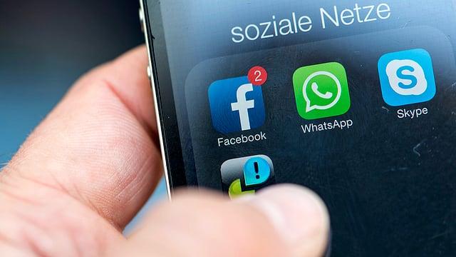 Männerhand die Iphone hält, Whatsapp und Facebook erkennbar