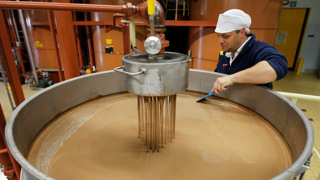Ein Mitarbeiter von Barry Callebaut prüft flüssige Schokolade in einem grossen Kessel