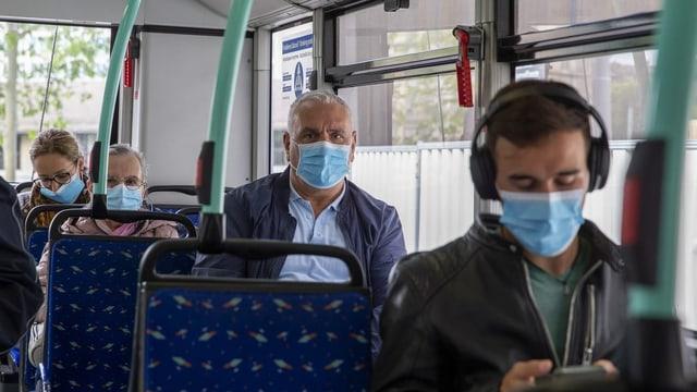 Passagiere im Bus mit Masken