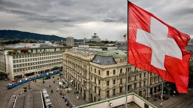 Zürcher Paradeplatz aus der Vogelperspektive, im Vordergrund eine Schweizer Fahne.