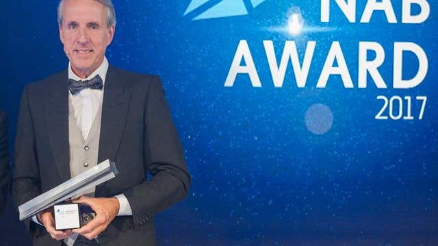 Markus Wopmann vor einer glitzernden Wand mit NAB-Award-Logo