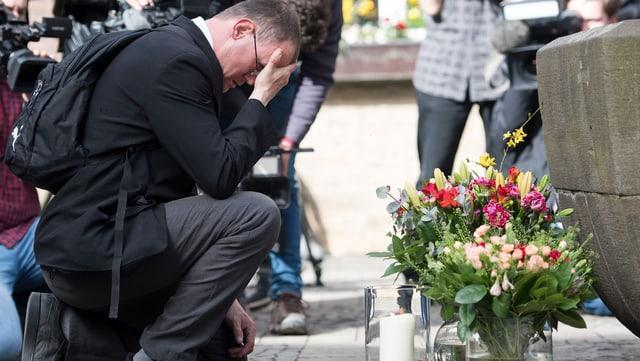 Ein Mann trauert, beobachten von zahlreichen Kameramännern, am Tatort.