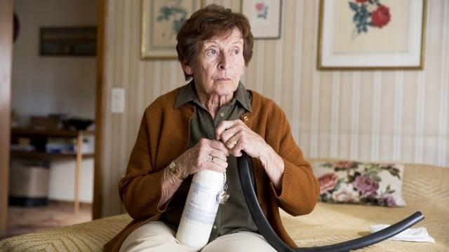 Eine alte Dame sitzt auf einem Bett und schaut gedankenverloren in die Ferne