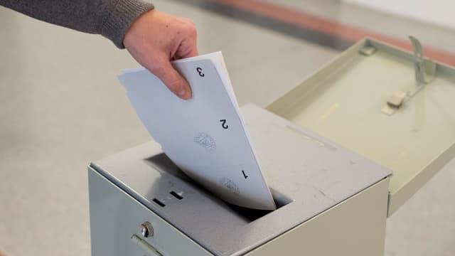 Jemand wirft einen Abstimmungszettel in eine Urne.