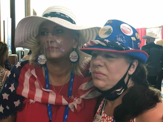 Zwei Frauen tragen Hüte, Anstecker und Schals