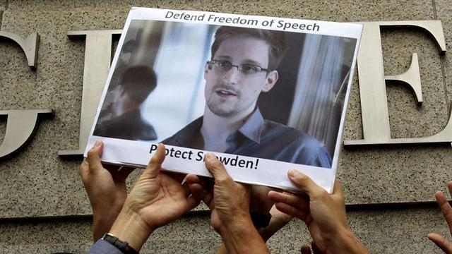 Snowden-Anhänger halten das Plakat des Ex-Geheimdienstmitarbeiters hoch.