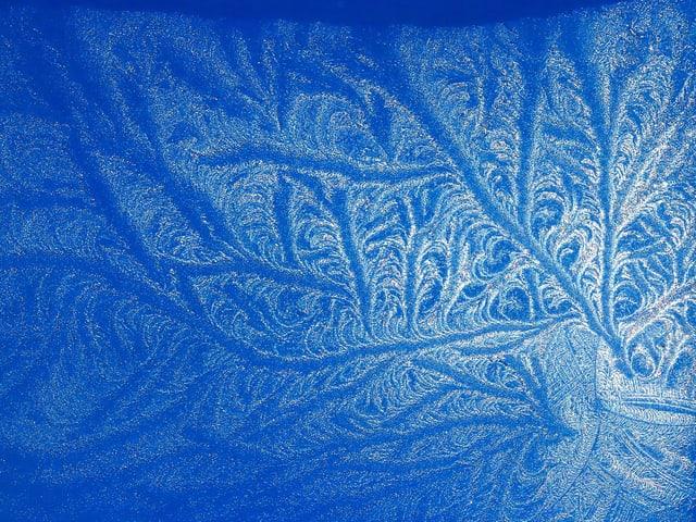 Eisblume am Dachfenster mit blauem Himmel als Hintergrund