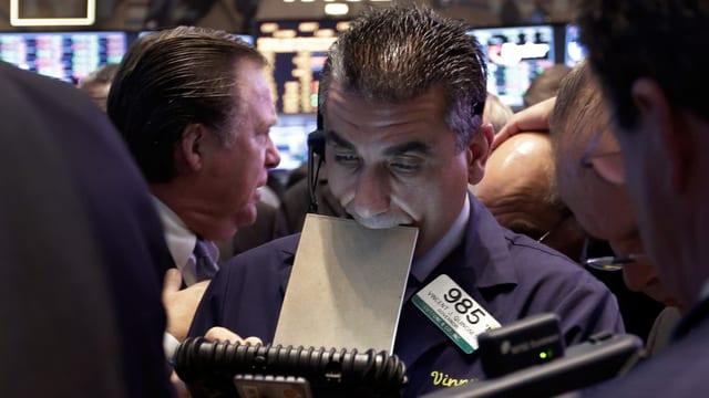 Ein Börsenmakler mit Block im Mund in der New Yorker Börse.