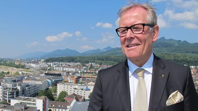 Ernst Zingg trägt einen Aanzug mit schwarzem Blazer, weissem Hemd, beiger Krawatte und beigem «Poschettli». Im Hintergrund die Martinskirche und die Stadt Olten, sowie die Jurakette.