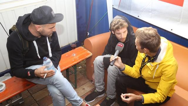 Livio Chistell (dre.) intervistescha Tobias Rieser (san.) e Adrian Held (amez), ils dus DJs da Klangkarussell Live.