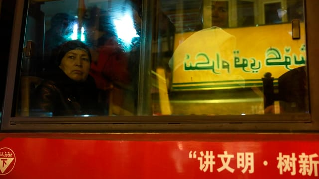 Eine Frau sitzt in einem Bus. Der Bus ist chinesisch beschriftet und fährt an einer Tafel mit arabischen Texten vorbei.