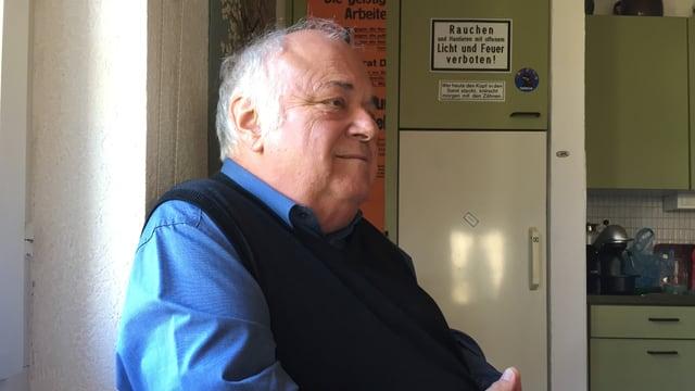 Ein Mann sitzt in einer Küche.