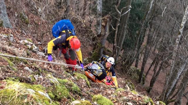 Zwei Retter mit Helmen halten eine Art Rettungsschlitten mit dem Patienten